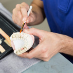 Closeup Of A Dental Technician Applying Porcelain To A Mold