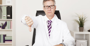 Sad Male Doctor Showing Thumbs Down